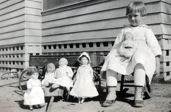Little girl sitting beside her doll collection, circa 1920?