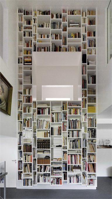 Modern interieur met hoge speelse boekenkast, de aangebrachte spiegel reflecteert een deel van de tegenoverliggende raampartij waardoor een verrassender en minder streng beeld ontstaat dan als de spiegel daar niet zou zijn.