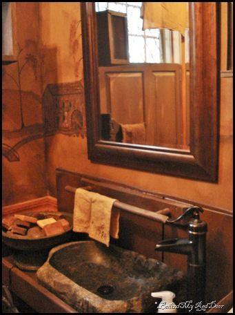 wonderful powder room.. mural on the wall . great sink.