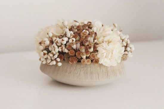 Modern dried flower arrangement. A low design mixed with small poppy pods, white tallow berries, and creamy white preserved hydrangea blooms tucked into a low cement bowl with a textured rim.