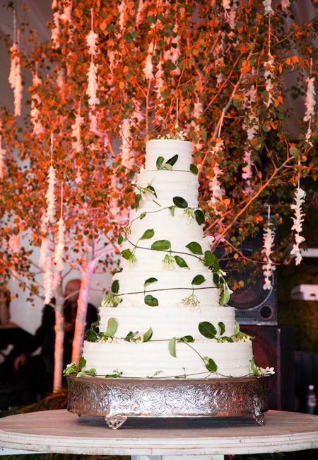 Brides.com: Simple white wedding cake covered in fresh vines