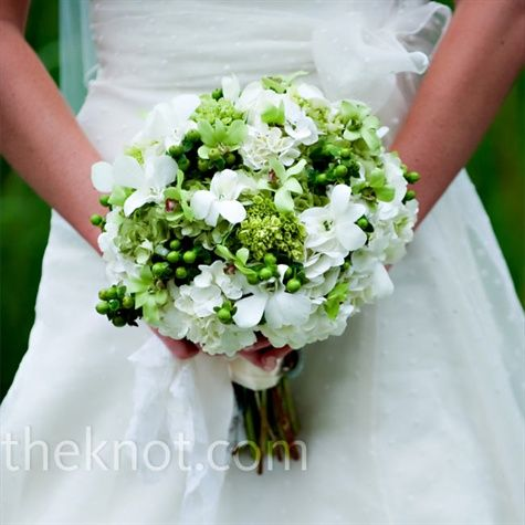 Katy loved her white and green bouquet of hydrangeas, orchids, and hypericum berries. An ivory satin ribbon stitched with the wedding date and adorned with her great grandmother's blue earrings personalized the bouquet.