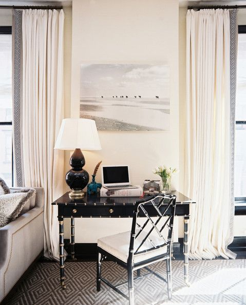 White curtains and a gray couch beside a black desk and chair.