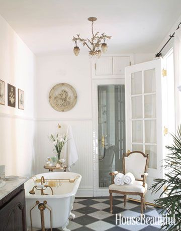 The sink base is an 18th-century French buffet with Kohler fixtures. Design: Karyl Pierce. Photo: Kerri McCaffety. housebeautiful.com. #bathroom #bath #white #antiques #french_doors
