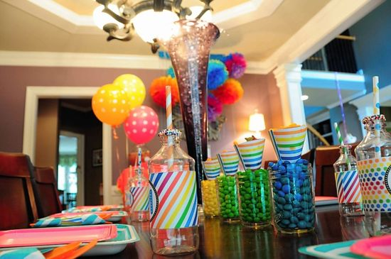 bright colored tissue paper poms in background. and different colored m+m's
