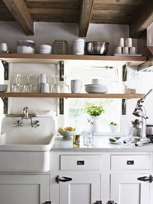 An extra-deep farmhouse sink and convenient shelving make clean up a breeze in this kitchen. #decorating