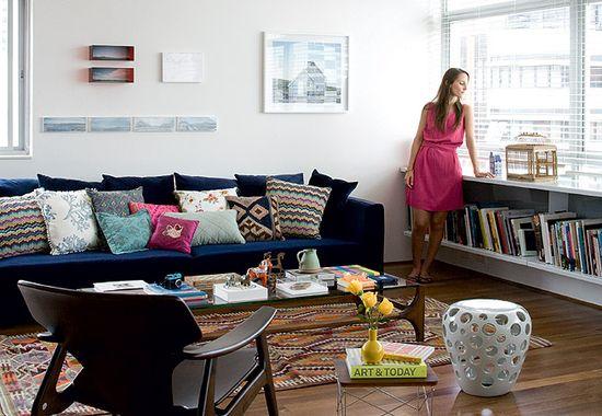 Na sala de estar deste apartamento no bairro dos Jardins, em São Paulo, uma extensa persiana na cor branca controla a entrada de luz no ambiente. Sob a janela, um móvel de madeira organiza livros e revistas sobre artes plásticas