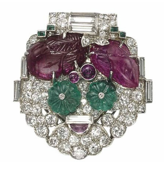 AN ART DECO RUBY, EMERALD AND DIAMOND 'TUTTI-FRUTTI' BROOCH, BY CARTIER   Of shield-shape, set with brilliant and baguette-cut diamonds, decorated with carved rubies, cabochon rubies, fluted emerald beads and calibré-cut emeralds, 1920s, 3.4 cm  Signed Cartier, no. 3419517