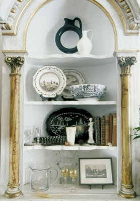 A bookcase made from antique furniture and filled with some modern accessories