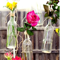 Sweet and simple hanging bottle vases greet guests in the backyard.
