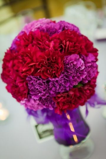 Kracke Photography image sphere shaped centerpiece of mounded carnations in purple and magenta by Stacy K Floral