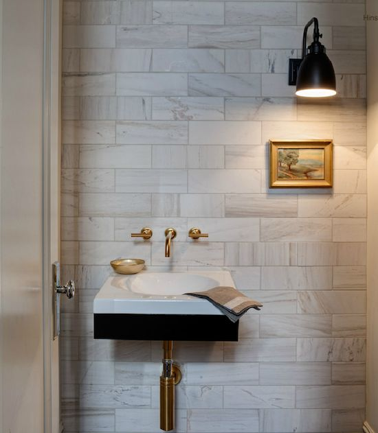 Beautiful powder room with marble subway tile backsplash and modern black bathroom vanity with gold wall-mount faucet with lever handles by Kohler. Oil-rubbed bronze sconce and bathroom art.