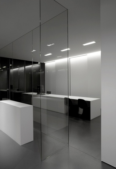 Black and white minimalist office with white large desk and glass partition_