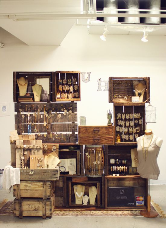 Wooden boxes, drawers and a barrel showcase the earth-tone jewelry in this display.