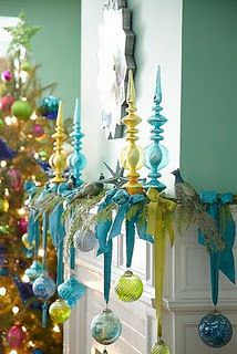 Hang Christmas ornaments from ribbons on the mantle