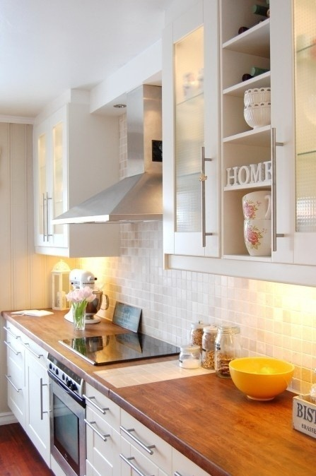 Simple kitchen - white cabinets, glass tile backsplash, wood countertops