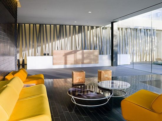 Bright Office Lounge With Yellow Lounge Sofa And Round Glass Tables