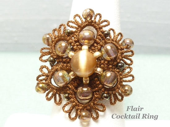This Cocktail Ring is a handmade shuttle-tatted Flair flower with dark gold and bronze Czech glass beading tatted into the edge. The 100% Egyptian cotton cord is mocha and is the color of chocolate, a wonderfully neutral brown.    The center is embellished with brighter gold glass beading and a large brown Cat's Eye bead for more sparkle. The tatted flower is secured to a dark bronze ring base with a permanent resin.