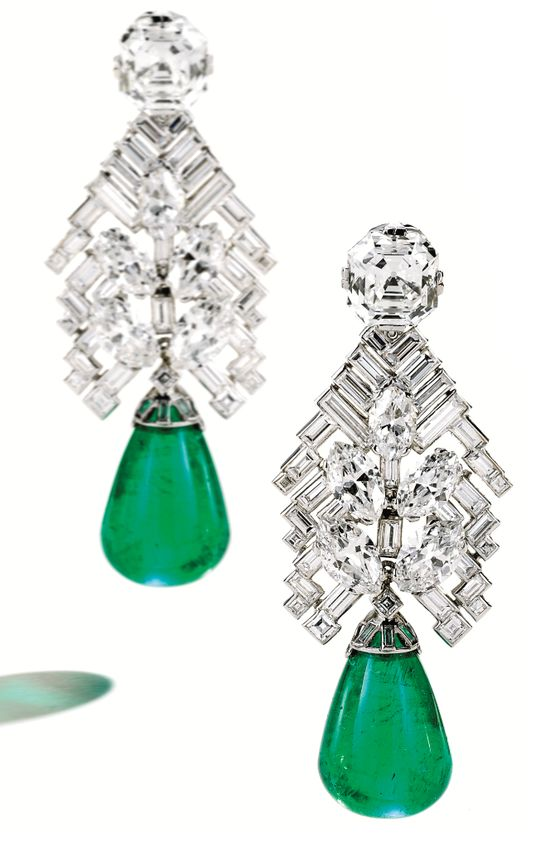 Art Deco emerald and diamond earrings by Cartier, circa 1934. These earrings are topped by one emerald-cut diamond weighing 4.78 carats and one cut-cornered rectangular step-cut diamond weighing 4.77 carats. The diamond surmounts suspend an articulated chevron motif set with numerous baguette, square-cut and marquise-shaped diamonds weighing a total of approximately 11.25 carats. These suspend two emerald drops, together weighing approximately 50.30 carats. Via Diamonds in the...
