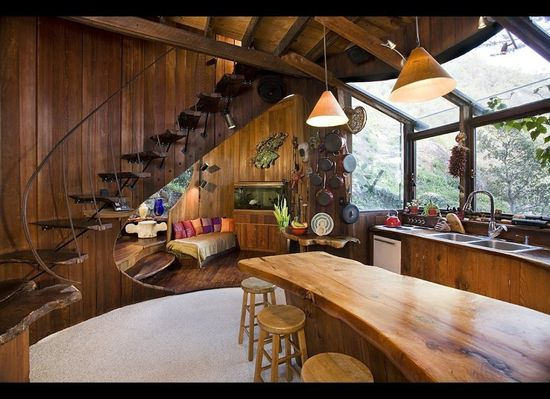 """In 1982, Breen had moved from Lansing, Michigan, to Big Sur to work as an assistant to artist Gregory Hawthorne, who had just relocated his home/studio there. Two years later, Breen set out to """"build the coolest wine barrel house ever."""" In his kitchen, a stair fashioned from redwood slabs and hand-forged steel provides access to the second-floor master bedroom."""