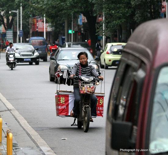 woman riding her scooter in Changsha, Hunan, China