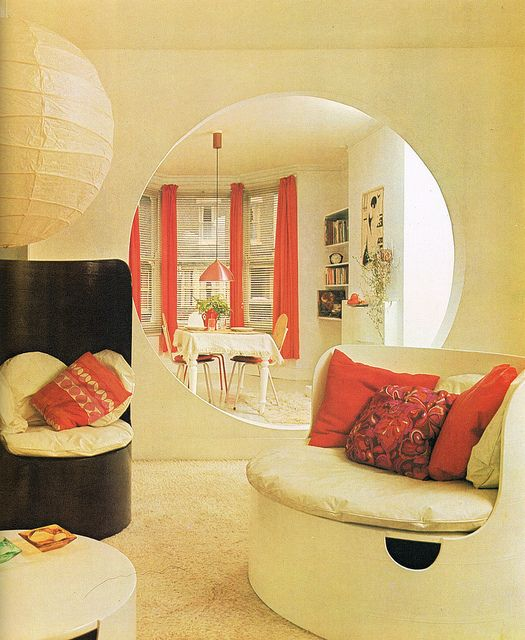 A 70s living room with a round port.  (Via Cat Rocketship, Offbeat Home)