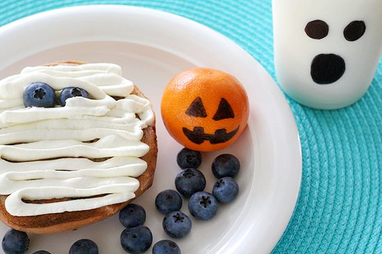 bagel with cream cheese and blueberry eyes. Clementine jackolantern drawn with sharpie