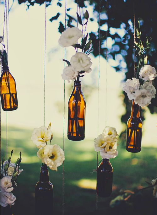 flowers in hanging wine bottles BUT w/ daisies.