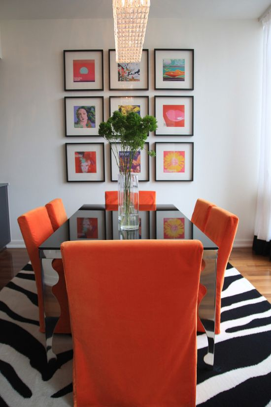 Eclectic dining room design with orange accents