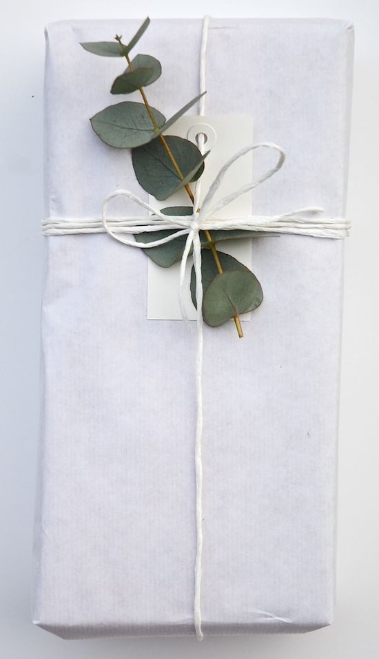 All white gift wrap with eucalyptus branch.