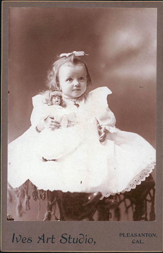 Old cabinet photo of adorable little girl holding her doll. Late 19th or early 20th century.