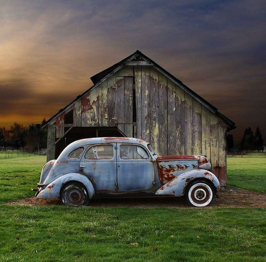 Love the weathered metal of the car and the multiple faded paint colors of the barn. Awesome picture.
