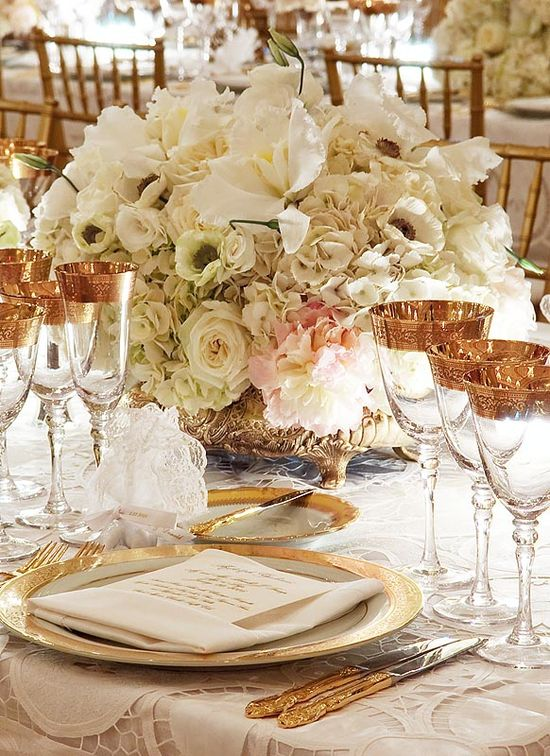 Gold rimmed goblets and plates with a white lace table cloth. The floral capturing the center of attention designed with a variety of white flowers resting in ornate gold bowl... Victorian revisited...or updated?
