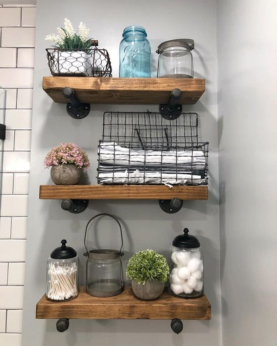 Warming up my gray, black and white bathroom with these great rustic wood shelves, some vintage wire baskets and pops of greenery & color.…