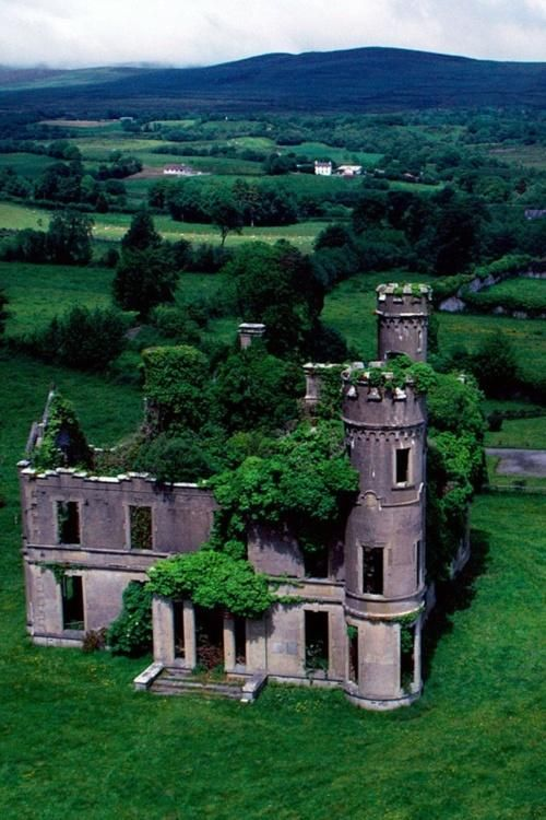 The green countryside of County Kerry, Ireland, slowly reclaims a castle near the village of Kilgarvan.