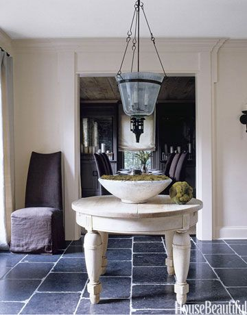 The juxtaposition of an oversize antique table and pale walls against dark bluestone floors has a quiet power. Design: Kay Douglass