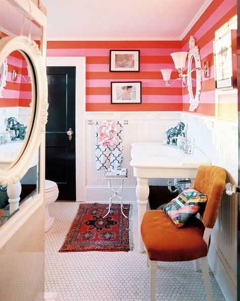 Pink-and-red stripes and white paneling and tile in a cheerful bathroom