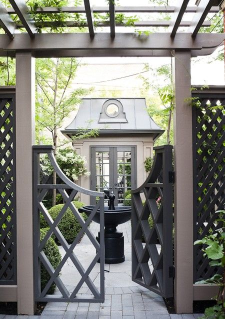 Designer Sharon Mimran. Chippendale-style gate and lattice fence lead the view into the private yard. Glimpsed from the street, the 7' by 7' storage shed resembles the Victorian style of the main house. Circular mirror and mansard roof.