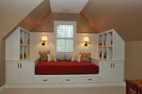 Great way to use bonus area with sloped ceilings! Custom built ins and daybed.