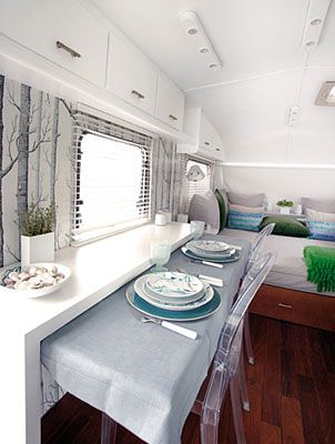 White & airy, with slide-out eating area.  Travel trailer by Caravanolic.