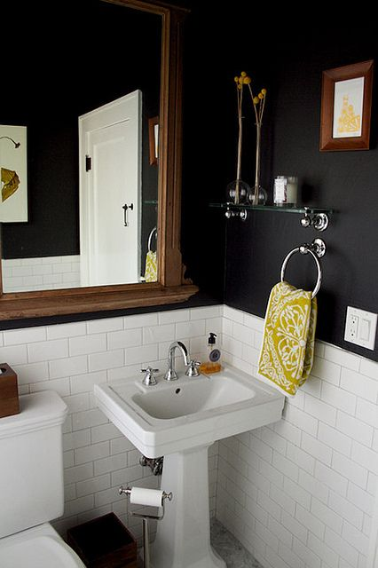 Black & white bathroom with mustard accents and wood details.
