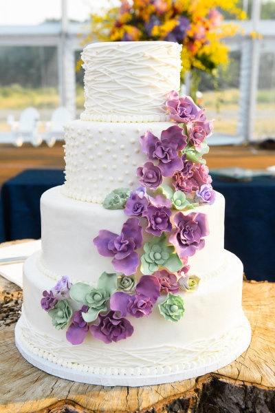 White wedding cake dotted with purple and green flowers.