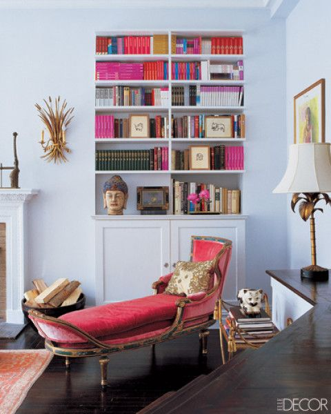 In Candace Bushnell's Greenwich Village, New York, apartment, a hot-pink, 19th-century Venetian chaise longue adds a dose of drama to a corner of the living room; the vintage gold-leafed sheaf sconce is one of a pair flanking the mantel, which is original to the apartment.    Photographer: William Waldron  Designer: Candace Bushnell