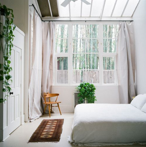 Image above: This room was originally used as a photography studio and was built in 1907. It is a wonderful bedroom to dream in with soft north facing light. The challenge to find find 15-foot-long curtains was met by utilizing large cotton painters drop cloths. The vintage Africa runner was paired with a single Danish chair.  2Gilda