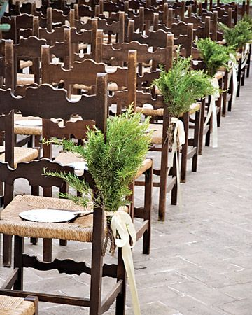 Bunches of rosemary tied to aisle chairs make a fragrant ceremony decor option