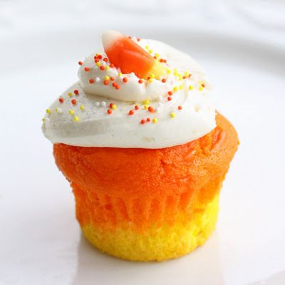 "Candy corn cupcakes. This is just regular cake mix with food coloring; they don't actually taste like candy corn. I love this ""doctored"" cake mix and homemade frosting recipe. I'll be making these all year round!"