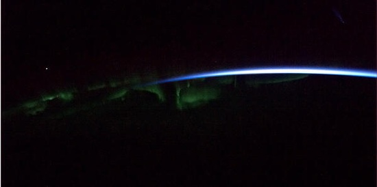 """Aurora dances above a ribbon of dawn."" Chris Hadfield from the International Space Station."