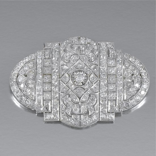 DIAMOND BROOCH Of open work design, millegrain-set with single-cut diamonds and centring on a principle circular-cut stone. Art Deco or Art Deco style.
