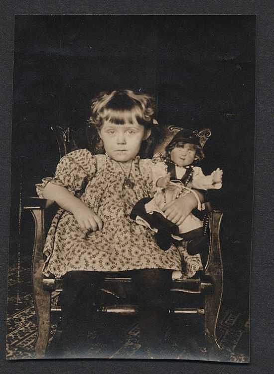 Little girl with sad eyes holding her doll, circa 1910-1920.