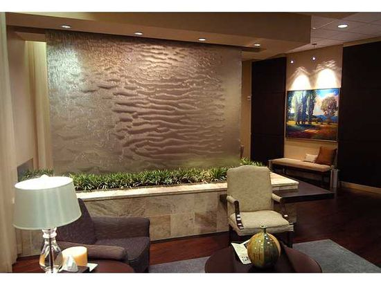 "Earth tones (sage, taupe, gray, brown), ""water feature,"" plants, artwork in a waiting area."
